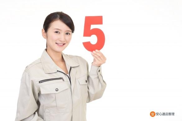 数字の5を持つ女性スタッフ